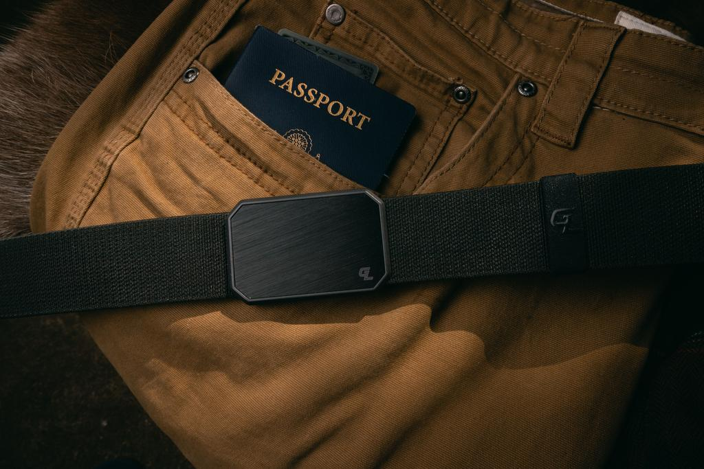 The Groove belt on top of some brown pants with a passport in the pocket.