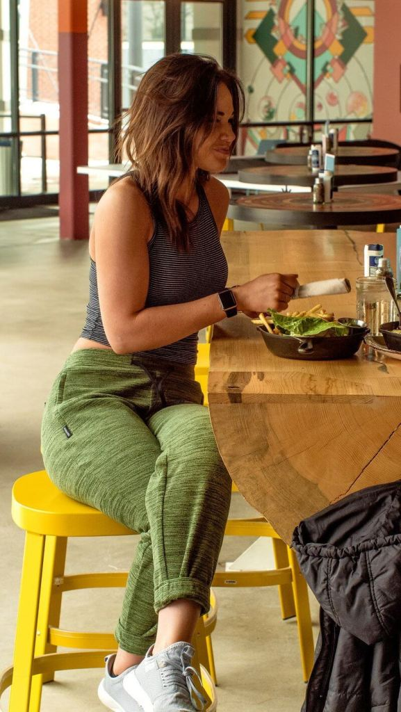 A woman wearing her Evolution Joggers from Coalatree while eating at a restaurant.
