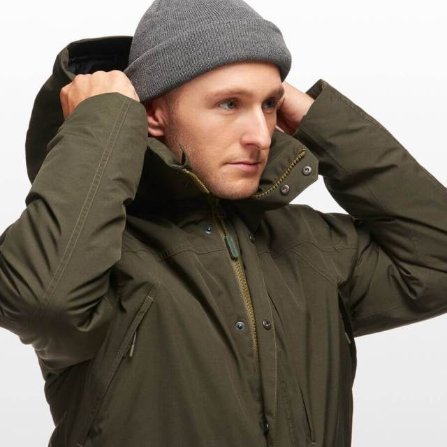A man wearing his green GORE-TEX down parka from Backcountry.