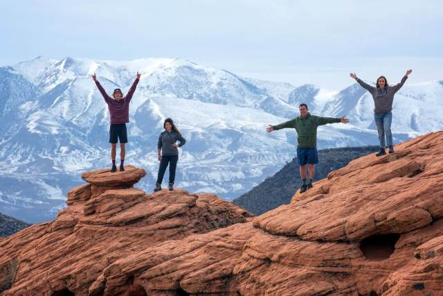 Two men and two women on the top of a large rock formation by some beautiful mountains as they wear their CoalaTree Evolution Hoodies.