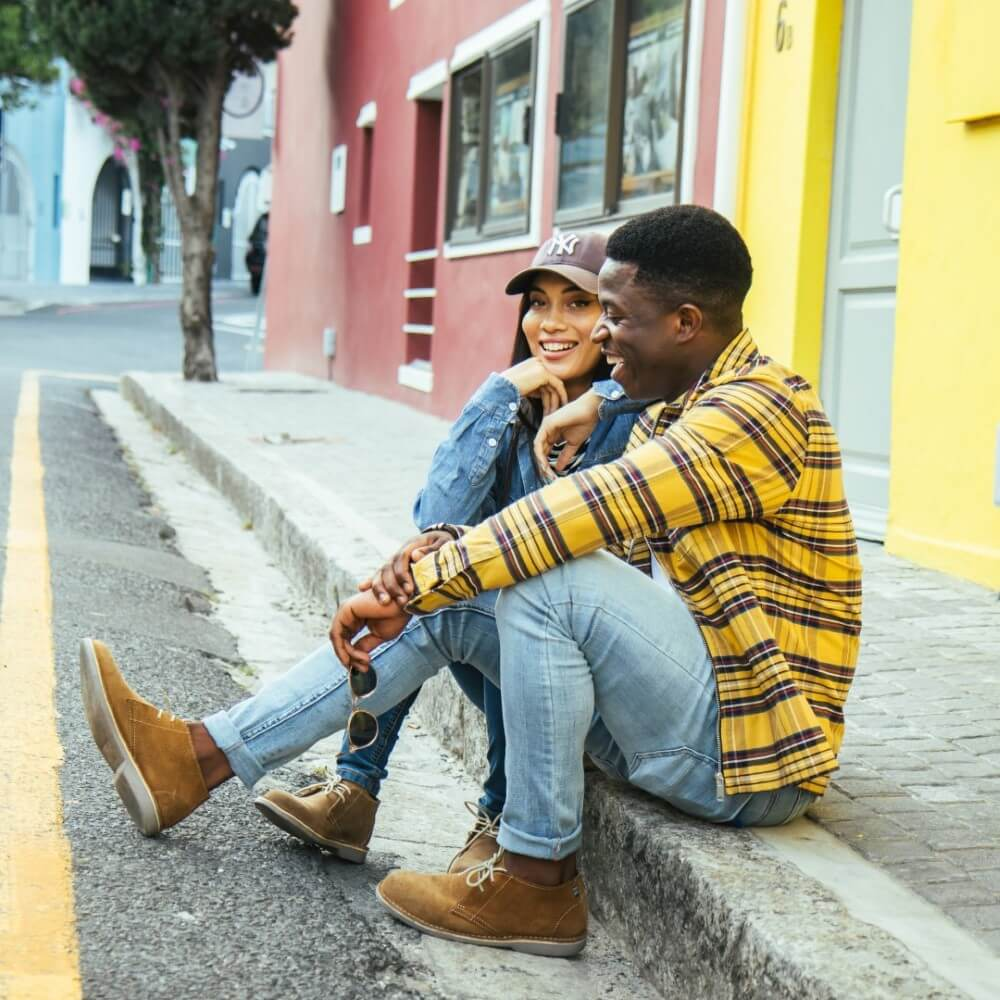 A man and a woman wearing their Veldskoen shoes as they sit on a curb next to some bright buildings.