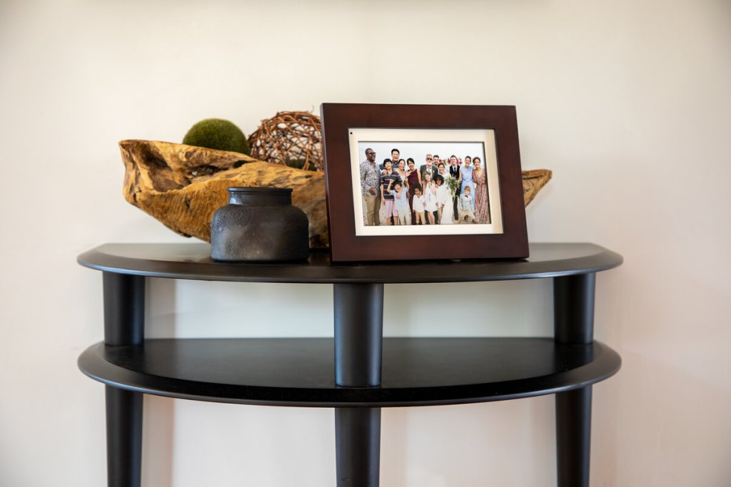 The Simply SmartHome PhotoShare Smart Frame on a decorative table as it displays a large family photo.