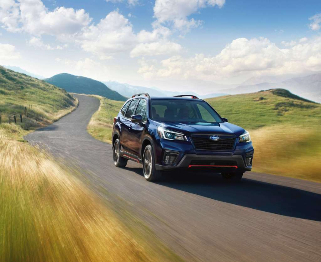 The 2021 Subaru Forester Sport driving down a country road.