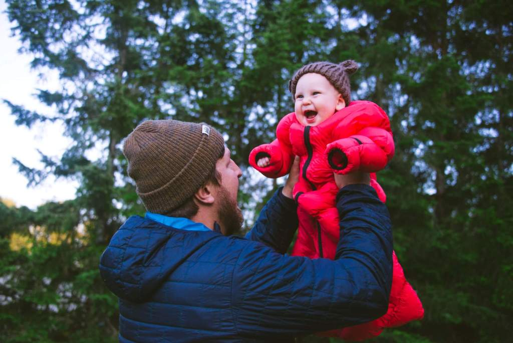 A dad holding his baby that is cuddled up and smiling inside the Morrison Outdoors sleeping bag.
