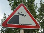 car off cliff sign