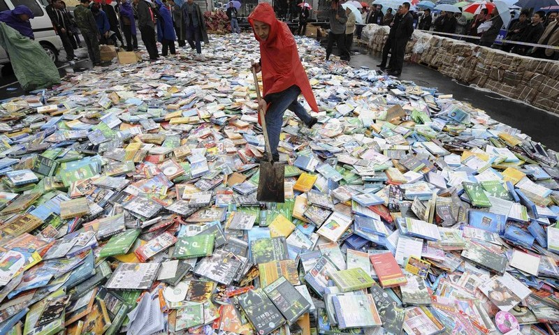 File photo shows a local official shovelling pirated DVDs before destroying them during a campaign in Taiyuan