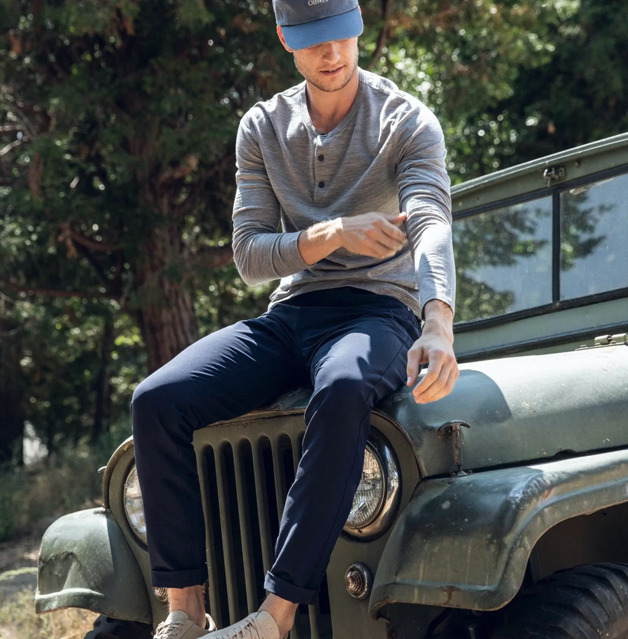 Model wearing Olivers Apparel Passage Pant, sitting on the front of a Jeep