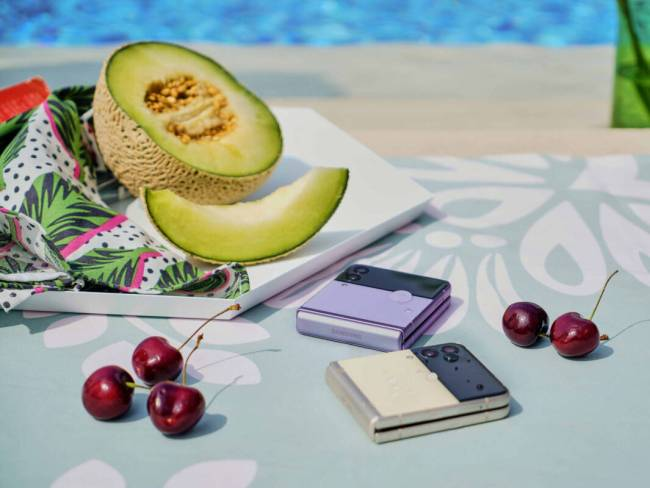Cherries, a sliced honeydew melon, and two Samsung Galaxy Z Flip3 phones by a poolside; I wish I was there right now