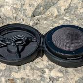Beyerdynamic PHONUM with open travel case showing the top of the speakerphone and the charging cable inside the travel case