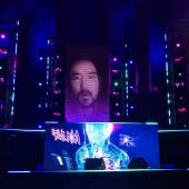 A stage with dramatic lighting and Steve Aioki's face on the screen.