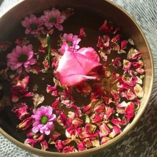 Duftschale mit Rosenblüten und ätherischem Rosenöl