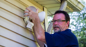 Electrician Putting Up A Motion Detector Light