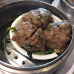Steamed Beef Balls served on top of watercress in a white bowl which is in a metal steamer.