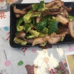 Pig lips with cucumber in garlic sauce served in a black rectangular serving dish.