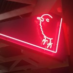 Red neon sign depicting a chick coming out of an alley or around a corner.