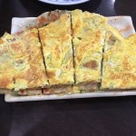 Green Onion Pancake with egg, served on an undersized white rectangular plate.