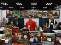 Stephen Buonocore of Stronghold Games behind his stronghold of games. Gamers have been chipping away at this wall all weekend—they breached the Dice Duel section entirely.