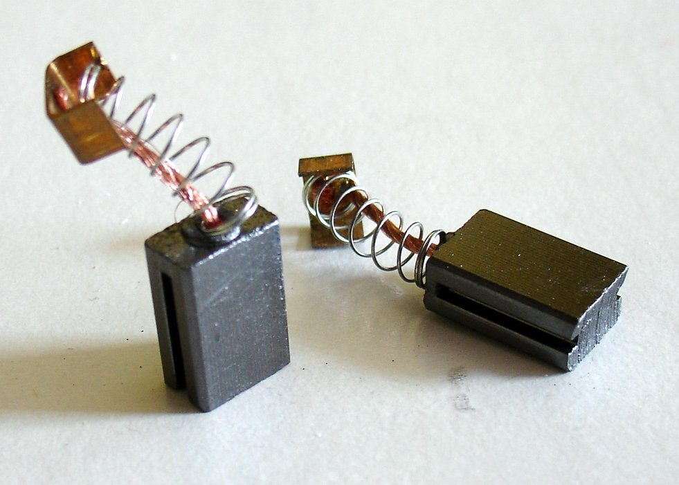 A picture of two carbon brushes, including springs, that are used with electric motors