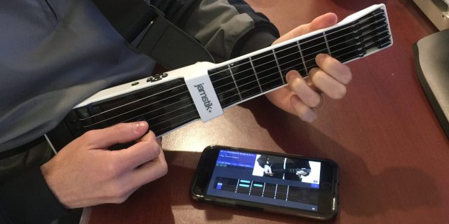 The jamstik+ is held with fingers fretting a D major chord. The jam Tutor app is open on an iPhone showing how to form the chord.