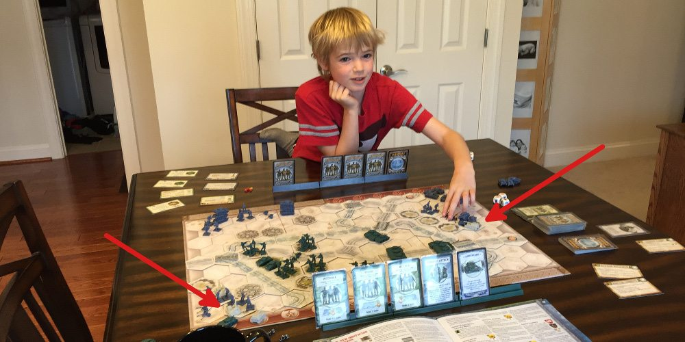 Child sitting in front of a set up game of Memoir '44 showing the unpainted Equipment Pack pieces.