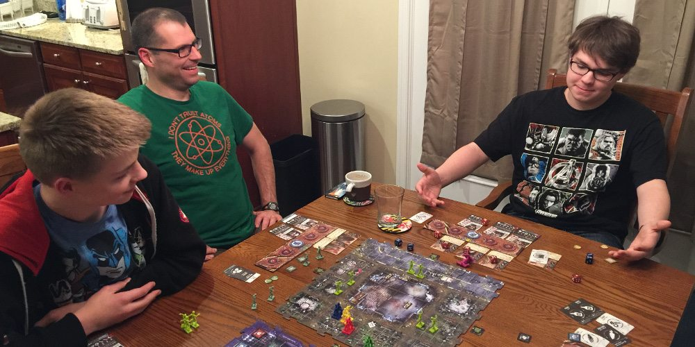 Three people playing Zpocalypse 2; one person has their arms pointed at their survivors and looks quite pleased with how the game has played out.