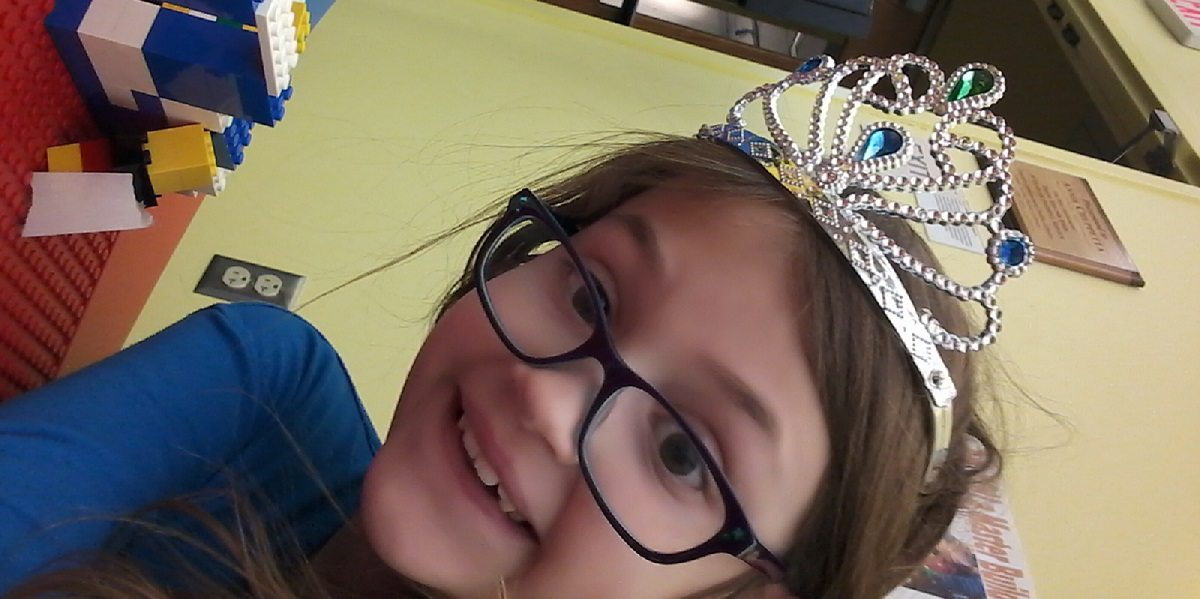 Bespectacled girl with tiara and Lego creation