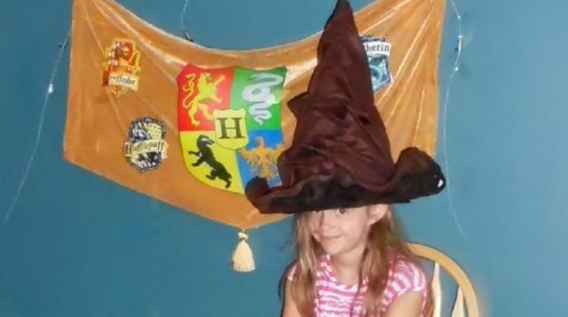 child in sorting hat in front of hogwarts banner