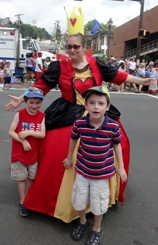 Author in Queen of Hearts costume in the middle of a parade route with two boys from the audience - first cosplay