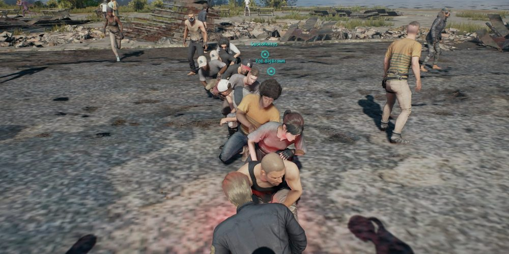 A line of players waiting in the pre-game area for 'PLAYERUNKNOWN'S BATTLEGROUNDS', crouched down and leaning left or right.