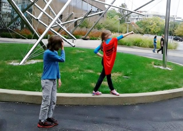 "Girl in ""Reading Gives You Superpowers"" cape poses in front of an outdoor sculpture, her brother looks embarrassed."
