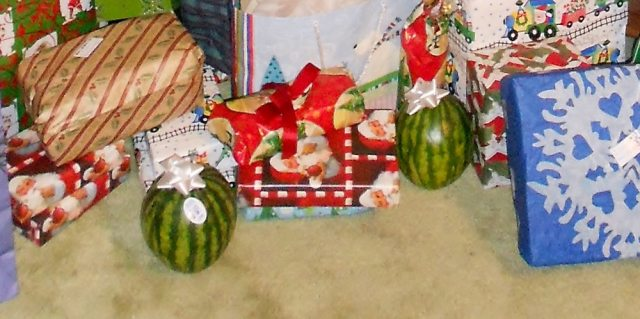 "two ""baby"" watermelon with bows sitting among other wrapped gifts"