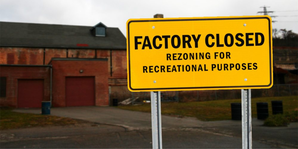 A sign in front of an old factory says Factory Closed, rezoning for recreational purposes