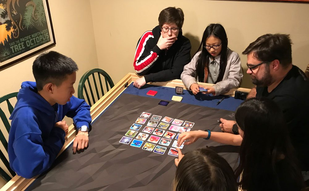 Group playing Codenames: Disney Family Edition