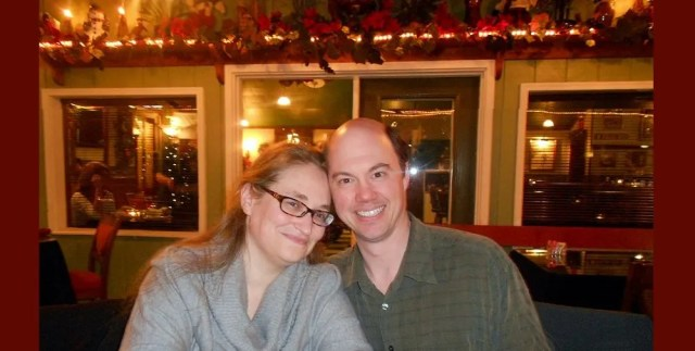 Author and husband in a Christmas-decorated romantic restaurant