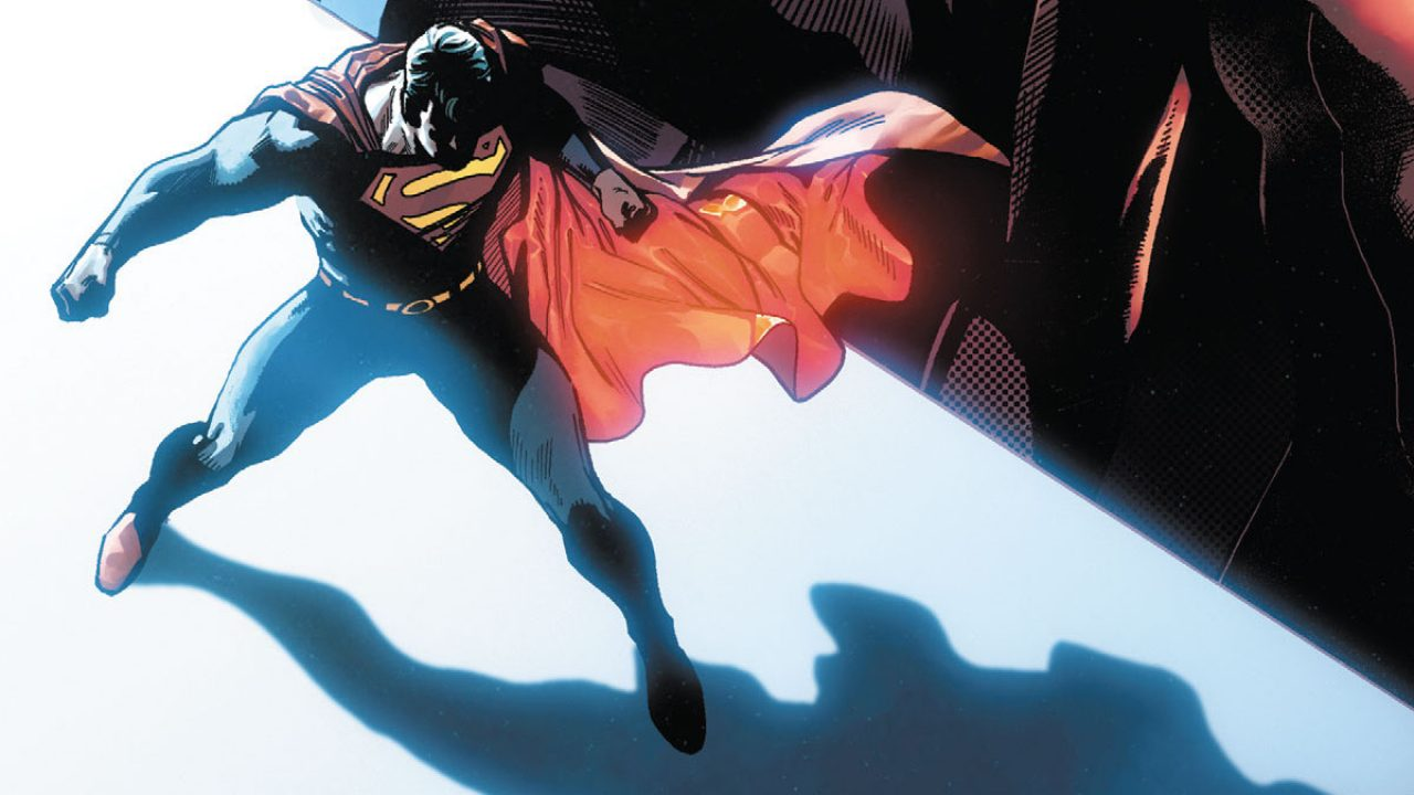 Superman's back is to the light as he walks into a dark room.