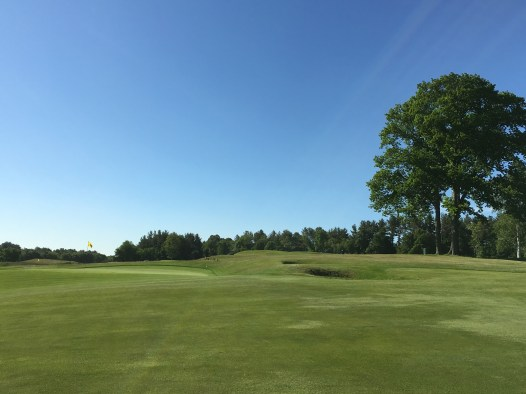 #1 - Par 4 - Approach to the green benched in the hillside