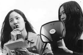 Asian American radical activists speaking at International Women's Day rally in San Francisco's Chinatown in 1971. Photo copyright © by Nikki Arai.