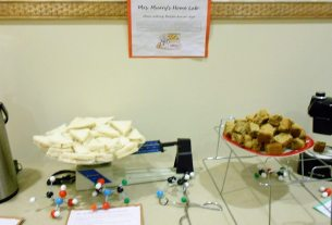 "Buffet table with hot drink dispenser, tuna sandwiches on a scale, cookies on a wire rack, and a stereo microscope, labelled ""Mrs. Murry's Home Lab"""