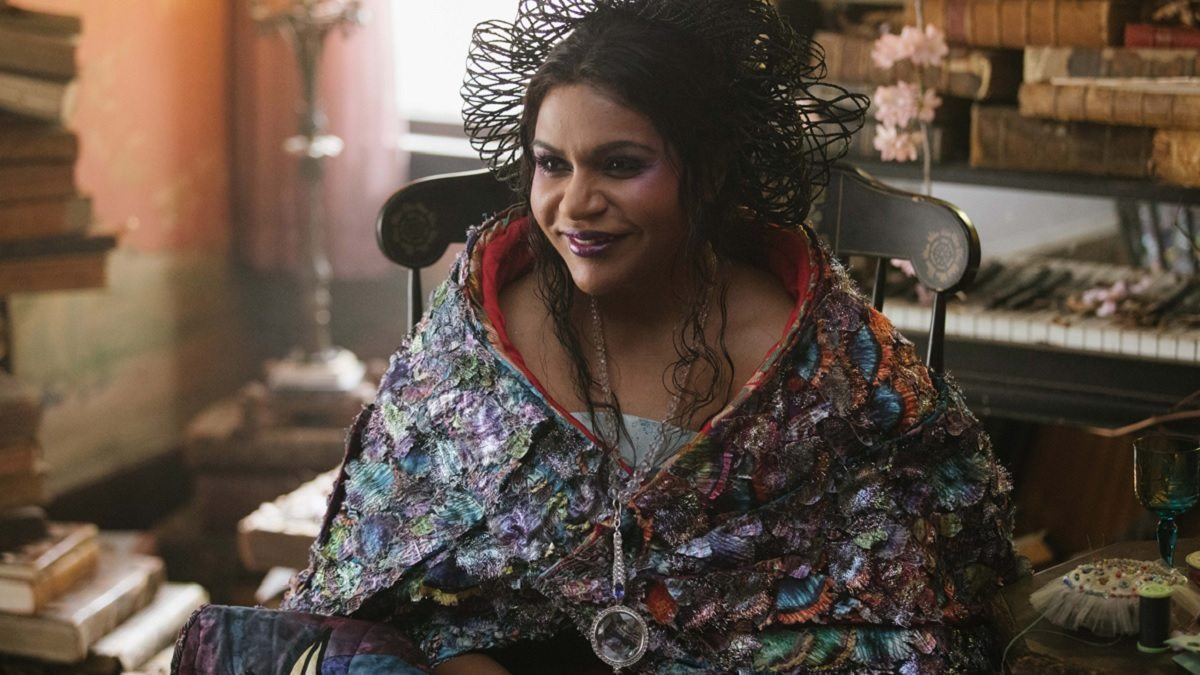 Mindy Kaling as Mrs Who surrounded by stacks of books in A Wrinkle In Time movie