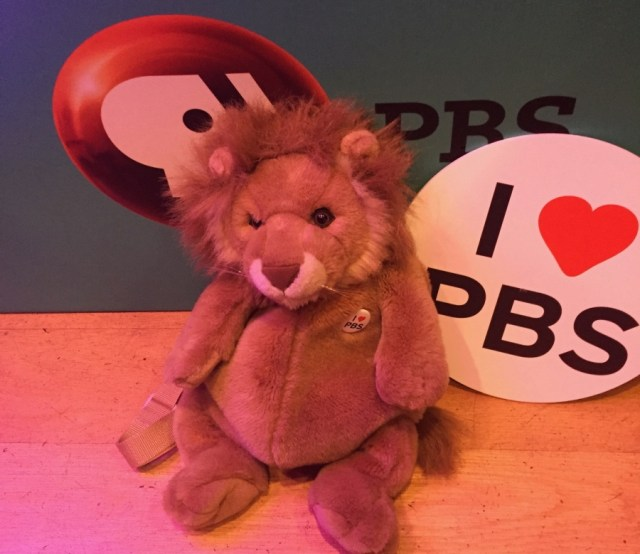 "a photo of a lion backpack on the floor at the Great American Read with a circular banner reading ""I [heart] PBS"""