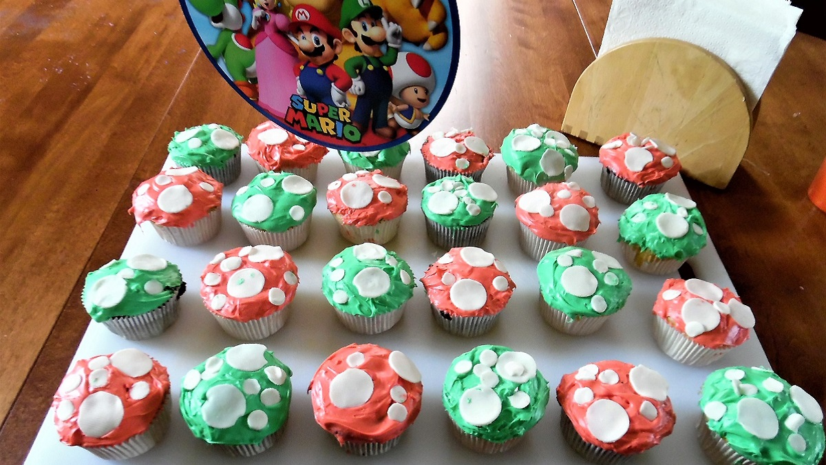 Tray of cupcakes, decorated like Super Mario powerup mushrooms, with white fondant polka dots on red or green icing.