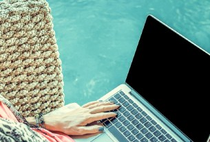 woman using laptop near swimming pool