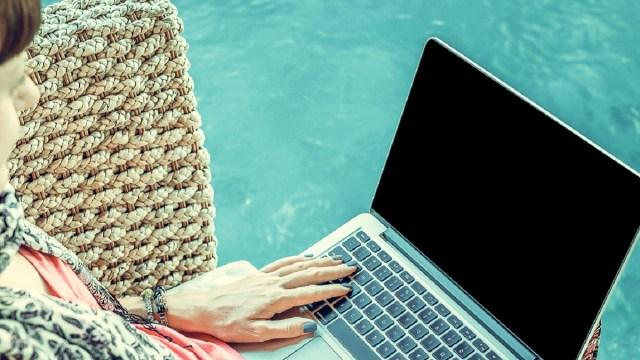 woman using laptop near swimming pool