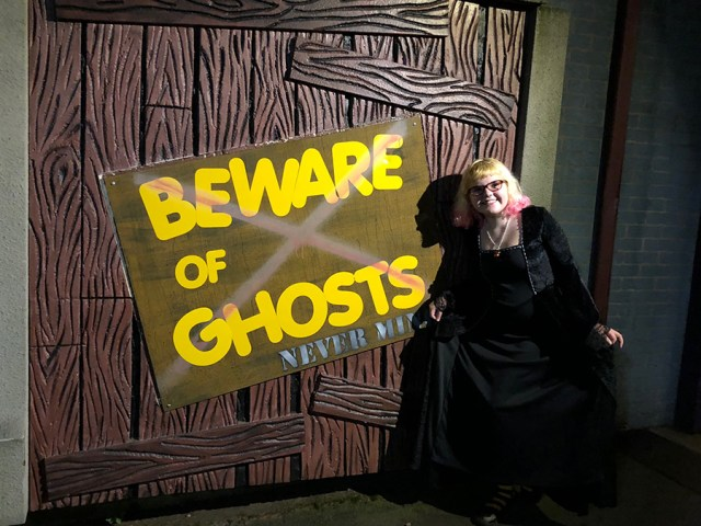 """a photo of the author's daughter in front of a tent stating """"Beware of Ghosts"""""""