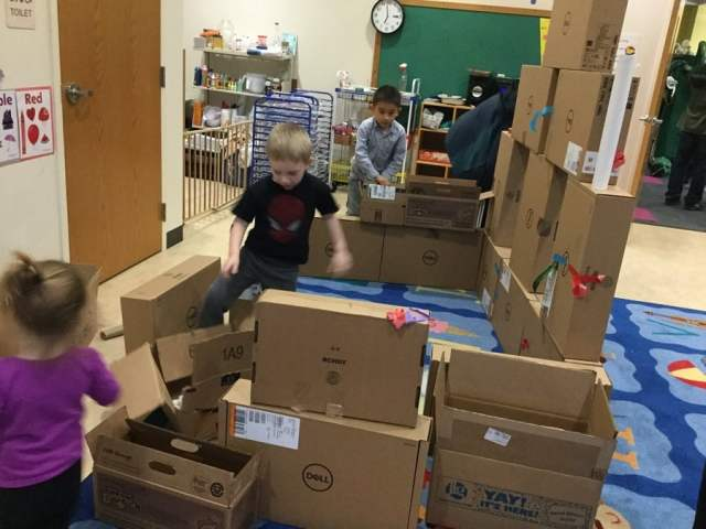 three children stacking rectangular computer boxes into a fortress