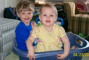 Two toddlers sitting in a laundry basket.