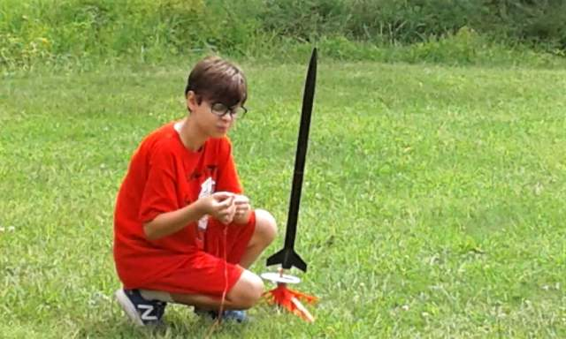 12yo hooking launcher wires to model rocket