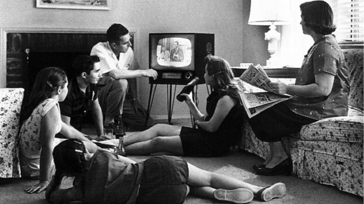 B/w photo of a Caucasian family made up of a man, woman, two teenagers and a preteen, watching television circa 1958