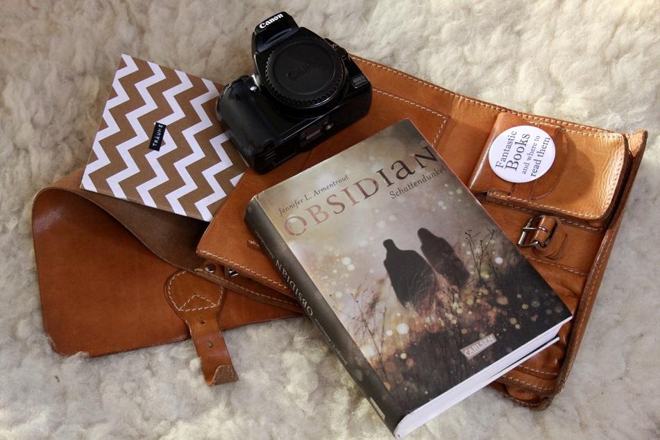 Das Buch Obsidian zusammen mit einer Kamera, einem Notizbuch und einer Ledertasche. Foto: Lilli/geek's Antiques