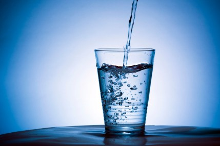 Cold water into a glass.